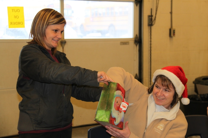 School bus driver Kim Kulyk draws for the next prize as electrician Brandy Links makes sure she doesn't peek during the Christmas potluck for Maintenance & Transportation at the Williams Lake Bus Garage.