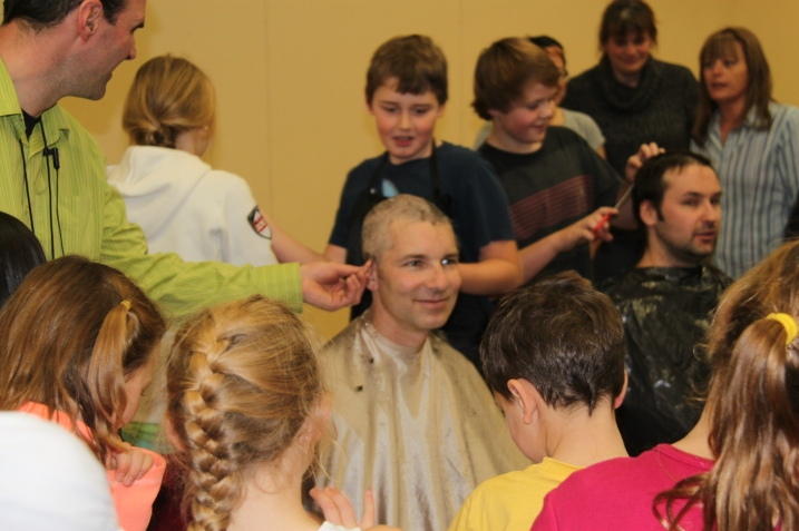 Cataline Elementary Principal Mike Grace literally bends the ear of Mr. Thiessen as three students from Cataline who suffer from diabetes work on a close haircut after a successful fundraiser.  In behind, teacher Chris Armstrong gets his head shaved due to funds raised for the Terry Fox Run.