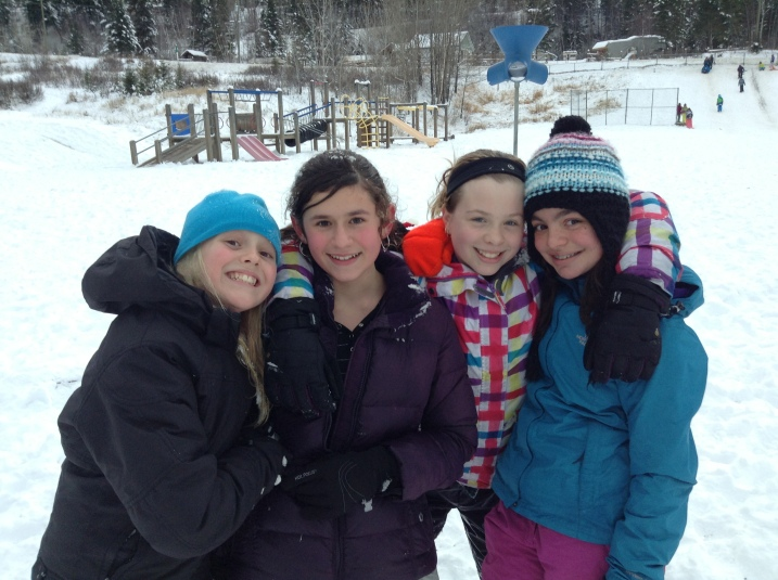 Four Chilcotin Road Elementary friends brave the cold and stay warm huddled up together.
