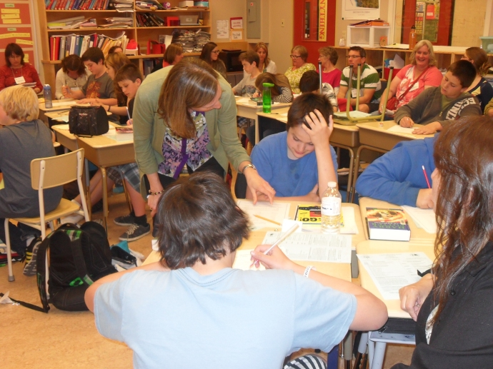 Adrienne Gear looks over a student's work at Cataline Elementary as teachers look on.