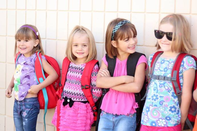 Four brand new kindergarten students wait outside Cataline Elementary during their first week of school.