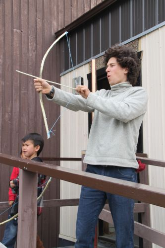 David Schein tries out his newly made bow as Naghtaneqed School students look on during the school's Cultural Week.